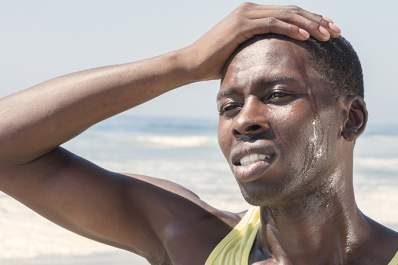 Man sweating on a beach.