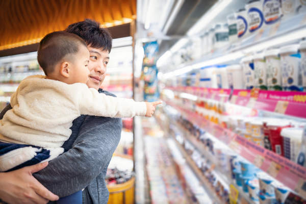 Man grocery shopping with his son in the dairy aisle.
