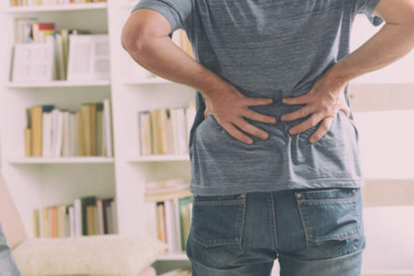 Man with lower back pain, holding low back with both hands.