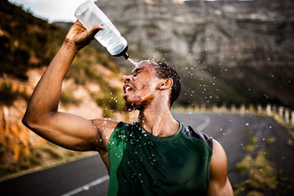 Man squirting water on his head during a run.