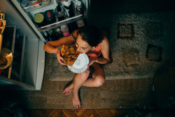 woman sitting on floor in front of refrigerator at night eating pizza