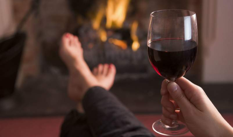 woman drinking wine in front of fireplace
