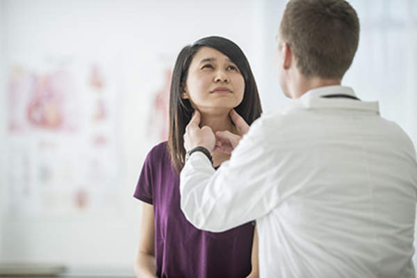 Doctor examining a patient's thyroid.