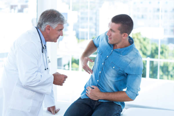 Man talks to doctor about intestinal pain.