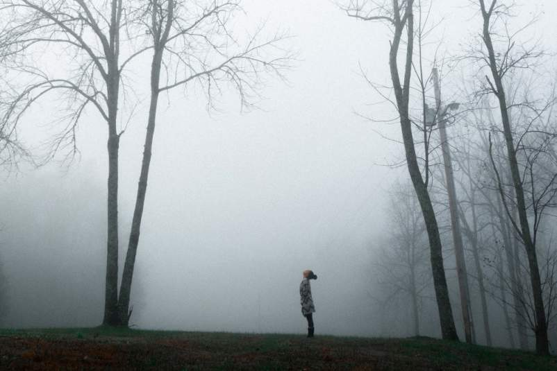 woman in the fog in the woods