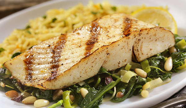 Grilled fish on top of greens.