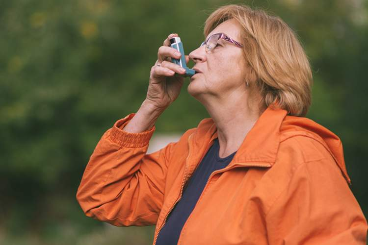 Senior woman using inhaler outdoors.
