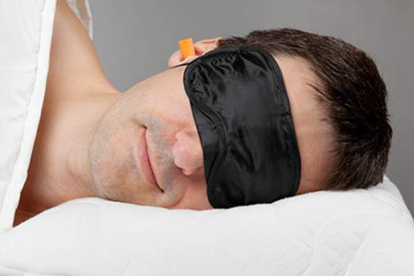 Man wearing eye mask and ear plugs to sleep.