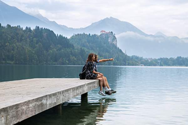 Couple sitting on a dock at a lake.