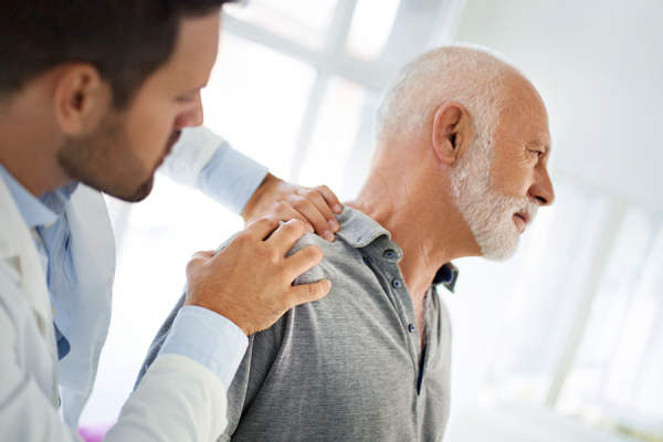 Doctor examining shoulder