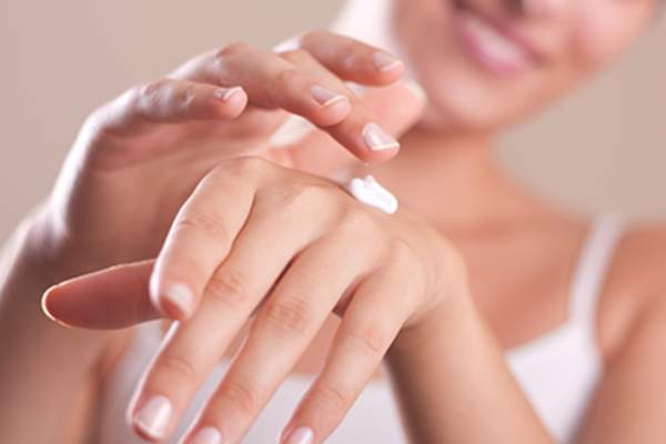 A woman applying lotion onto her hands.