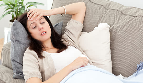 Woman lying on the couch and experiencing the symptoms of withdrawal.