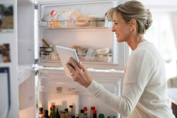 Woman getting food out of the refridgerator.