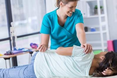 Smiling physical therapist working with female patient's hip.