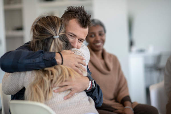 two people hugging during group therapy