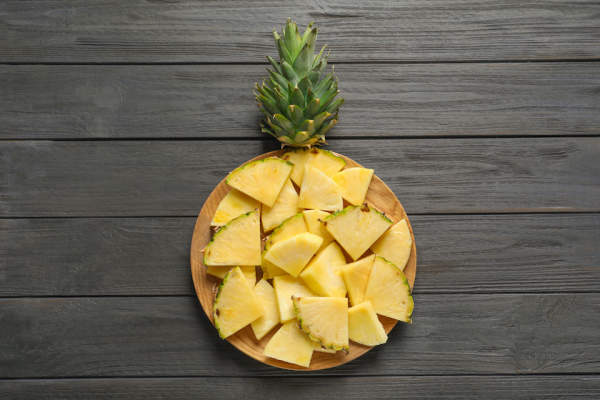 Pineapple cut up on round plate.