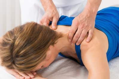 Woman receiving deep tissue bodywork for chronic pain.