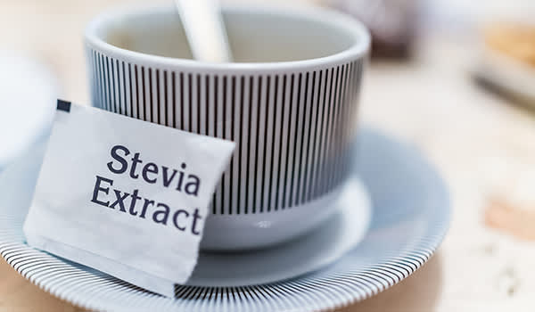Torn stevia extract packet next to a coffee cup.