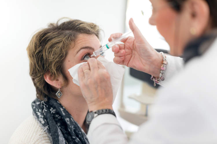doctor putting in drops before eye injection