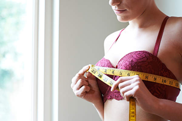 Woman measuring her bust size.
