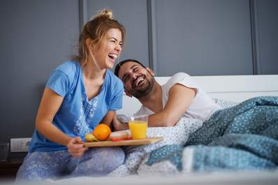 Young, smiling couple, breakfast in bed.
