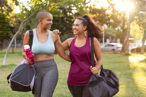 Two women, one with shaved head, walking together after workout