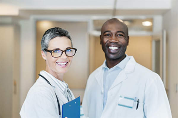 Smiling male doctor and female doctor in hospital.