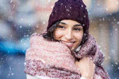 Woman smiling while bundled up in the snow.