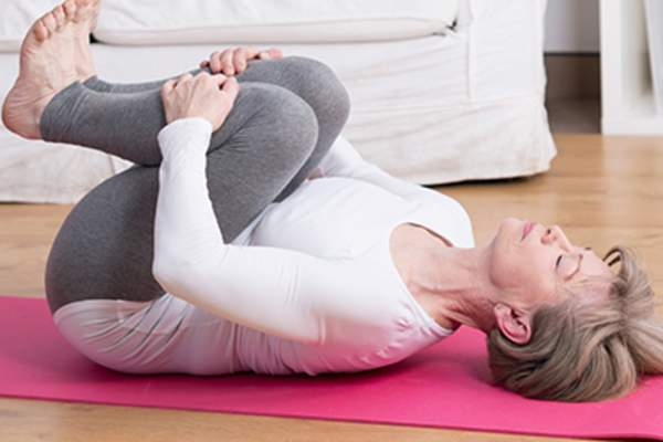 Woman using abdominal breathing techniques on a yoga mat.