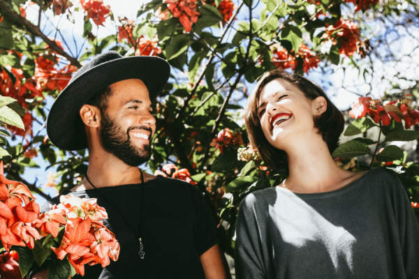happy laughing couple surrounded by flowering trees