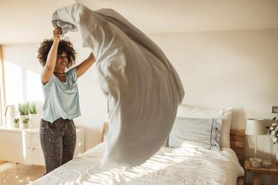 Woman making the bed in the morning.