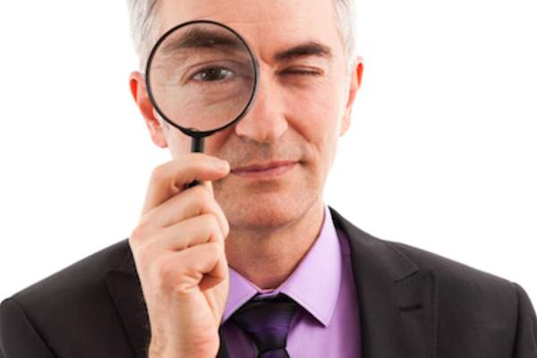 Searching concept man holding up magnifying glass.