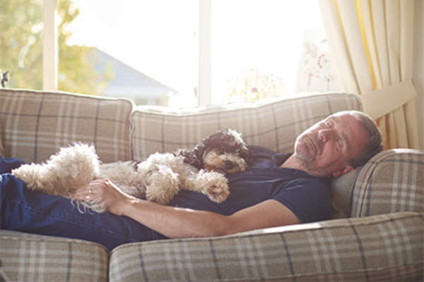 Man resting on couch at home with dog.