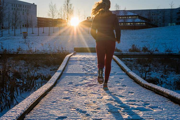 Woman jogging at sunset.