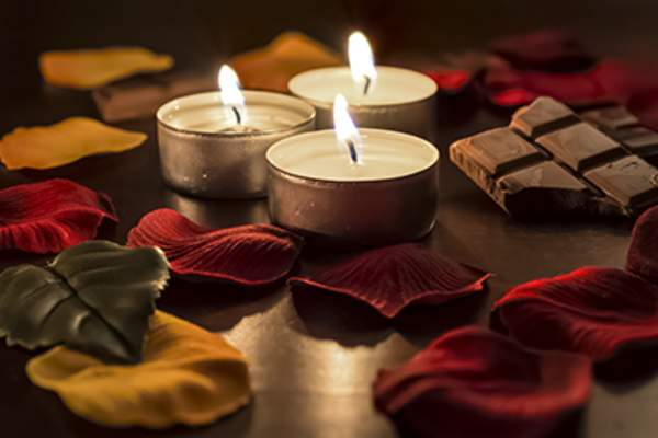 Romantic candles, rose petals, and chocolate.