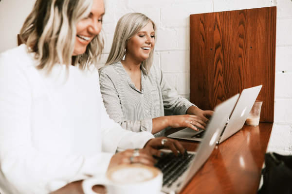 two women typing on laptops and smiling