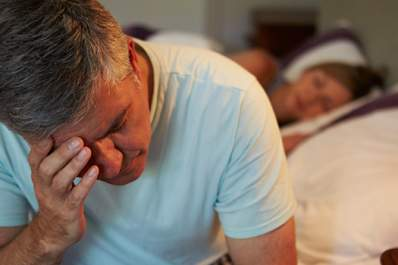Older man awake on side of bed frustrated.