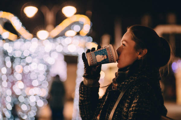woman wearing warm clothes drinking hot drink