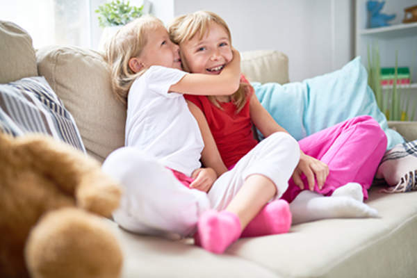 Young sisters smiling and hugging on couch.
