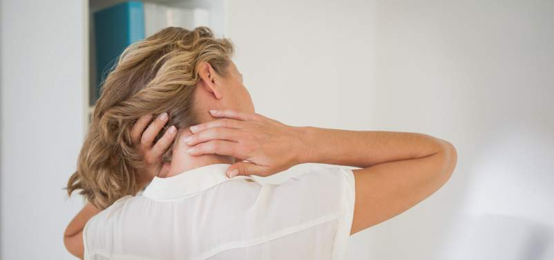 Woman touching back of neck