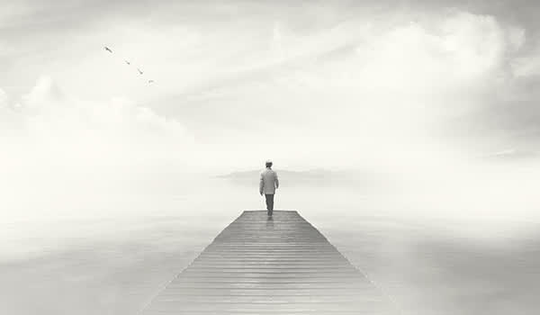 Man walking on boardwalk in fog.