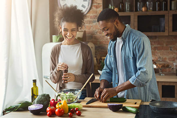Couple making a salad together.