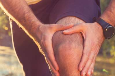 A runner with knee pain stops to hold his knee.