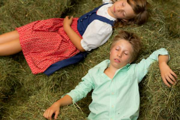 Farm kids sleeping on green hay bales.