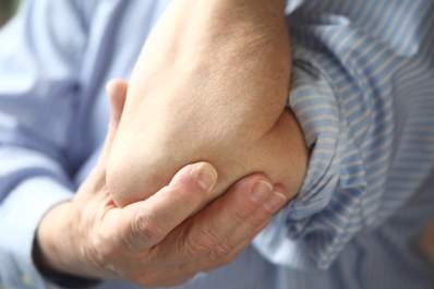 Man in pain with joints affected by severe rheumatoid arthritis.