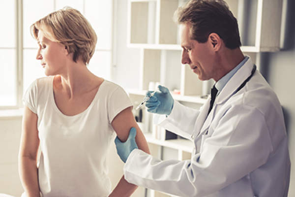Doctor giving a rheumatoid arthritis patient a vaccine.