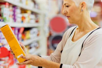 A woman reading nutrition labels in a grocery store.