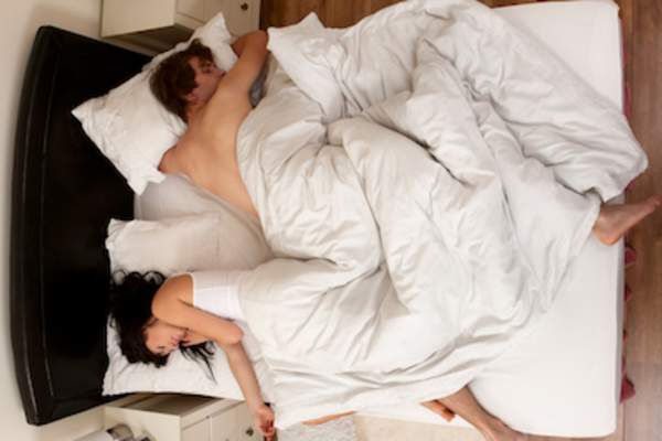 Couple in bed, man tossing and turning while asleep.