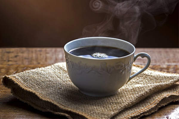 Steaming cup of hot coffee on napkin.