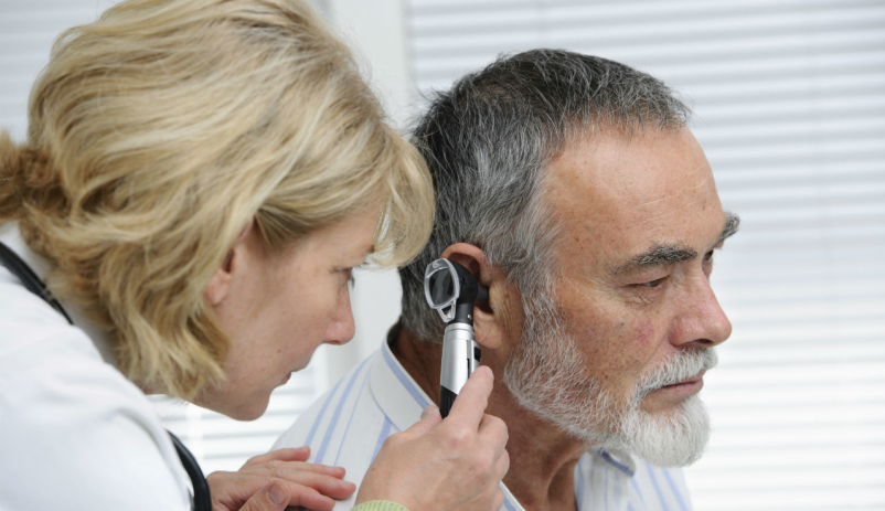 Doctor examining ear for ear wax impaction